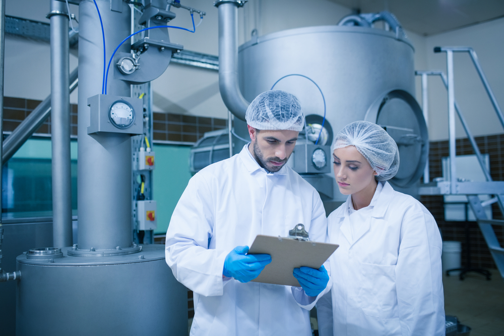 Food technicians working together in a food processing plant and the best mixing equipment